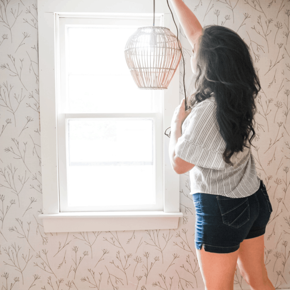 woman hanging up wooden light fixture. with wallpaper on wall