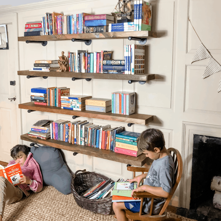 two boys laying under and bookshelf reading