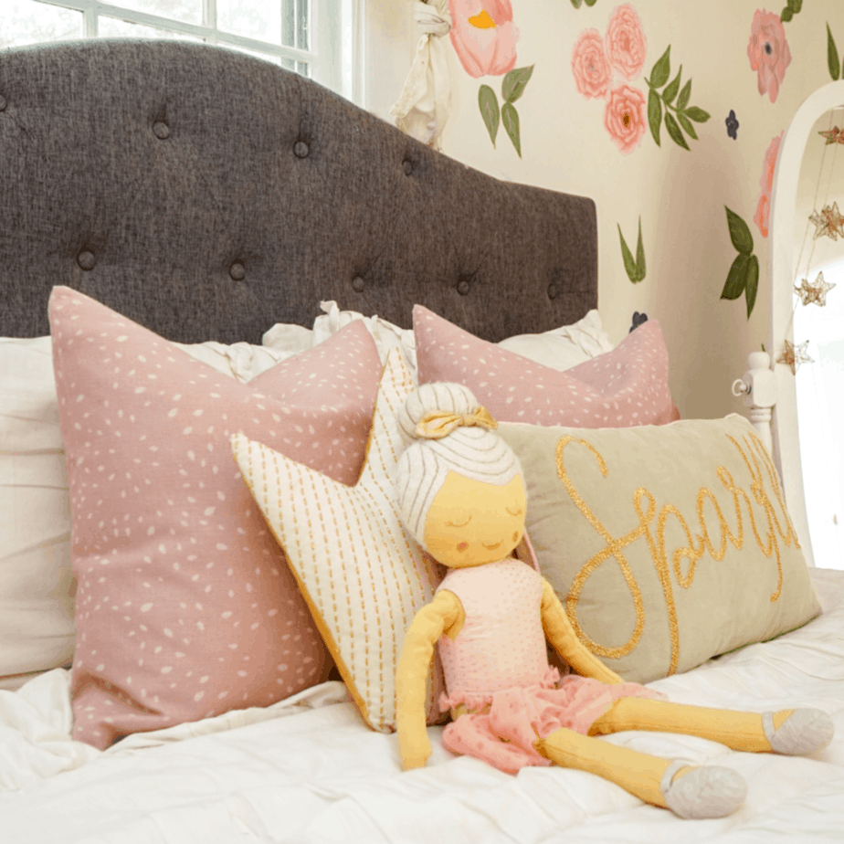 pink pillows on white bedding and doll stuffed animal