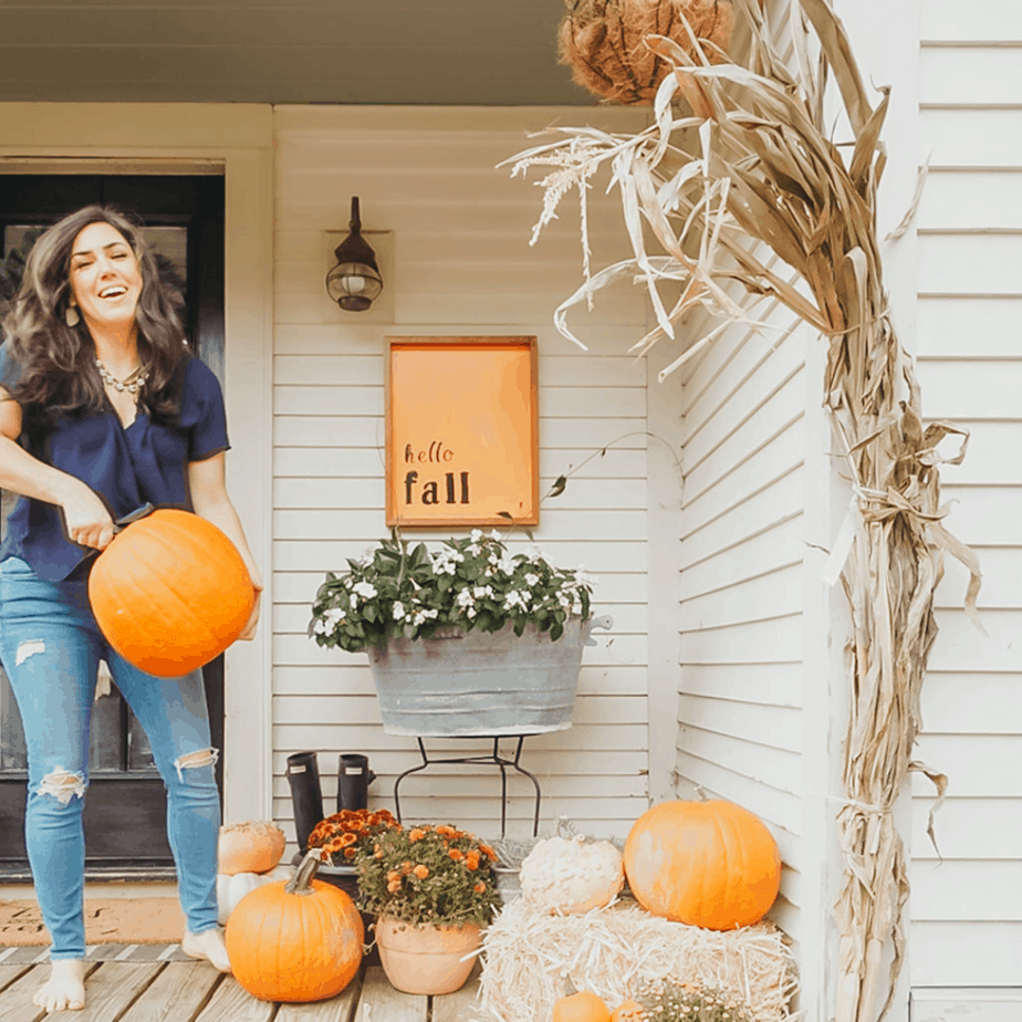 woman holding a pumpkin, corn stock on house, pumpkins and mums on front porch, and orange fall sign hanging on house