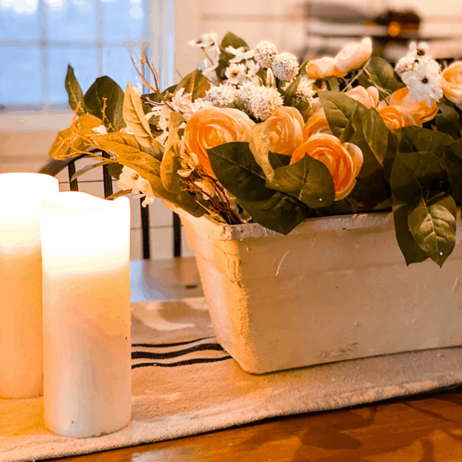 planter on table with flowers inside. candles on the table